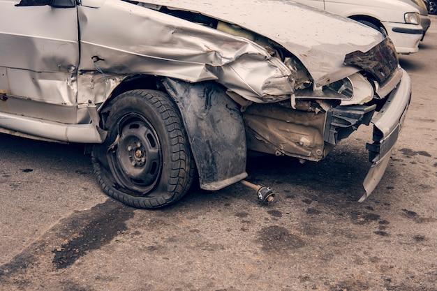 Close-up de um carro quebrado após um acidente de trânsito deixado no estacionamento. danos pesados em um para-choque e uma roda após uma colisão lateral. lado amassado de um carro como resultado de um confronto. clunker.