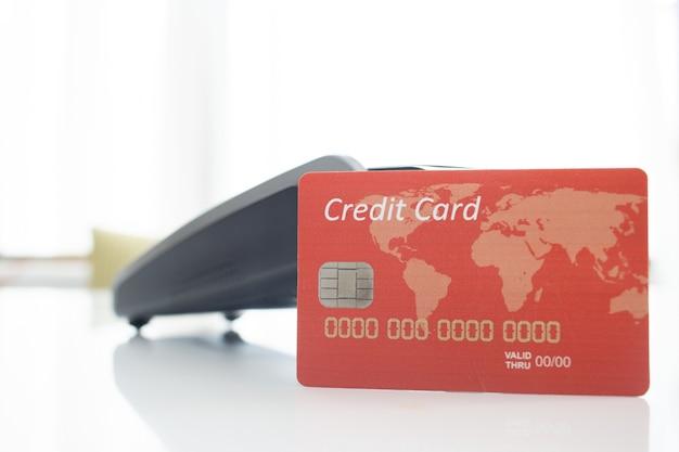 Close up de um cartão de crédito vermelho com um terminal de pagamento e um fundo branco desfocado