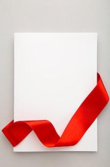 Close up de um cartão de nota com laço de fita na superfície cinza