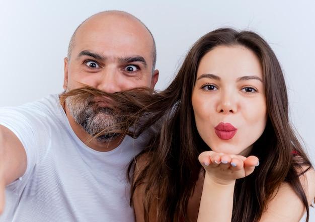 Close-up de um casal adulto brincalhão homem fazendo bigode com cabelo de mulher e mulher mandando beijo