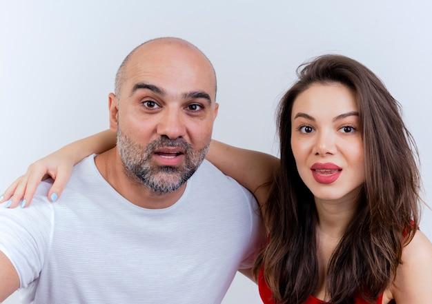 Close-up de um casal adulto impressionado, colocando a mão no ombro do homem e olhando