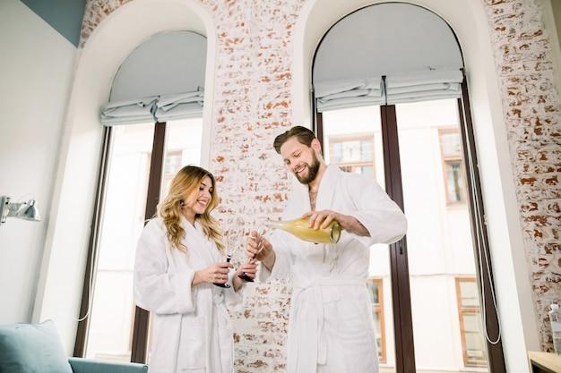 Close-up de um casal bebendo champanhe no quarto de hotel. homem bonito derrama champanhe em copos