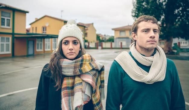 Close-up de um casal com roupas de inverno, em pé ao ar livre em um dia frio e chuvoso