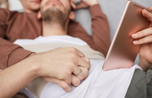 Close-up de um casal gay contemporâneo de mãos dadas enquanto está deitado no sofá e usando o tablet digital, copie o espaço