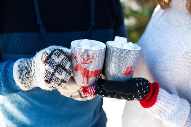 Close-up de um casal segurando copos com veados com uma bebida quente e marshmallows nas mãos em luvas de inverno quente