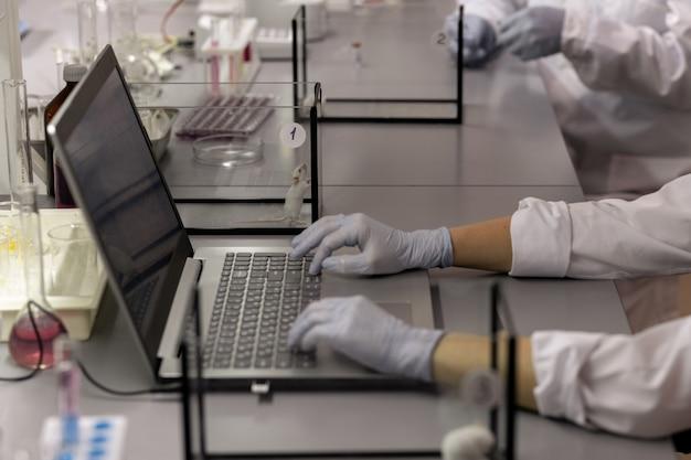 Close-up de um cientista com luvas de proteção, sentado à mesa e digitando no laptop enquanto trabalhava no laboratório