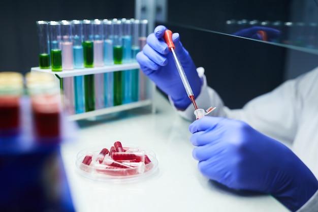 Close up de um cientista irreconhecível deixando cair amostras de sangue em tubos de ensaio enquanto trabalhava em pesquisas em laboratório, copie o espaço