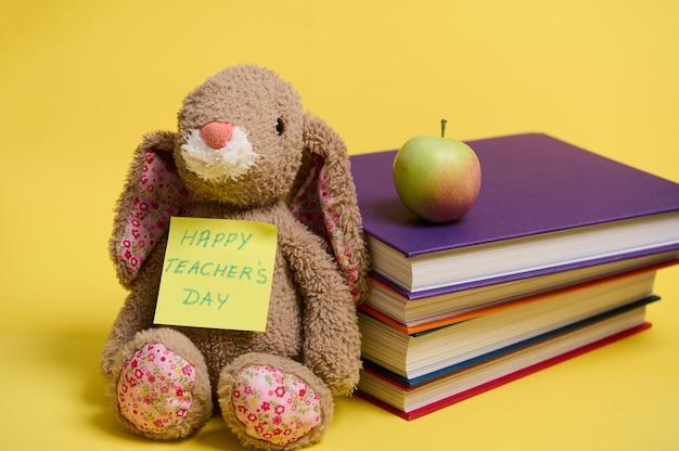Close-up de um coelho de pelúcia com a inscrição feliz dia do professor em um papel amarelo, apoiado em um monte de livros coloridos, fundo amarelo com espaço para texto