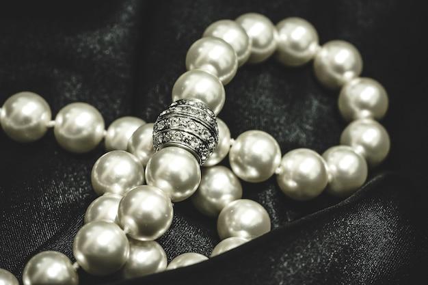 Close up de um colar de pérolas brancas com um fecho luxuoso
