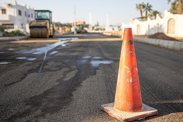 Close up de um cone de tráfego laranja no espaço da cópia da estrada