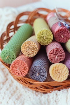 Close-up de um conjunto de velas decorativas de cera de abelha natural coloridas com aroma de mel para o interior em uma cesta em um suéter de tricô branco