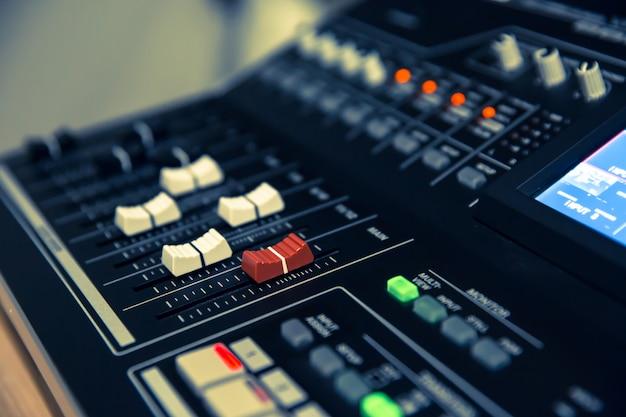 Close-up de um controle deslizante de volume no mixer de som profissional.