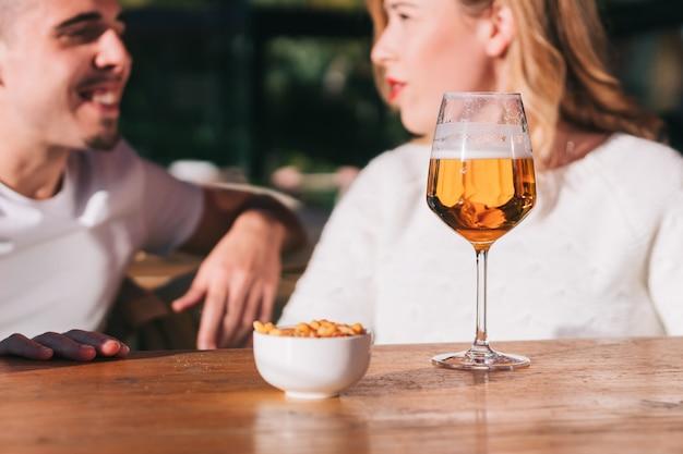 Close-up de um copo de cerveja na mesa de um bar, restaurante ou cafeteria. com um grupo de amigos conversando alegremente e sorrindo.