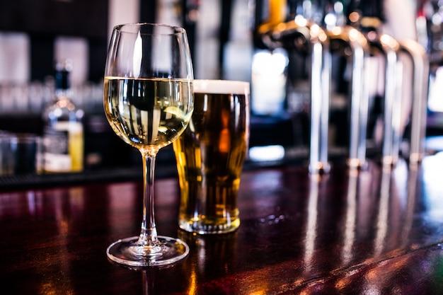 Close up de um copo de vinho e uma cerveja em um bar