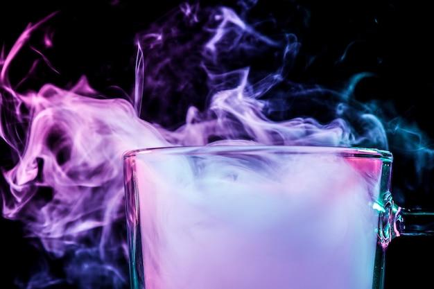 Close up de um copo transparente para cerveja cheio de uma nuvem de vapor rosa fuma e carrinhos