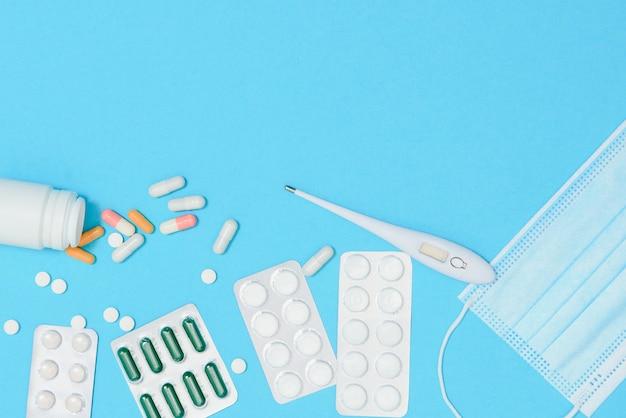 Close-up de um coração e um estetoscópio sobre um fundo azul, vista superior. conceito global de saúde. cuidar da saúde do coração. tratamento com comprimidos e ampolas