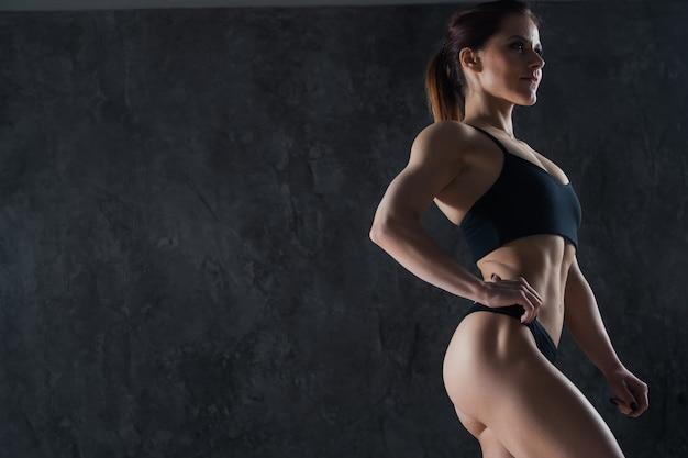Close-up de um corpo feminino perfeito sobre estúdio escuro