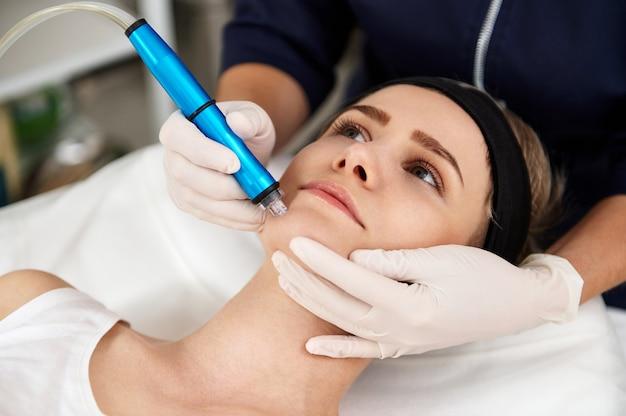 Close-up de um cosmetologista realizando um procedimento de peeling cosmético no rosto de uma jovem para esfoliar e limpar os poros