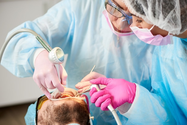 Close-up de um dentista e seu assistente em uma única vez, trabalhando com um homem paciente dentes