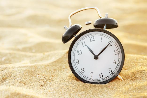 Close up de um despertador na areia de uma praia que ajusta a manhã do tempo de verão