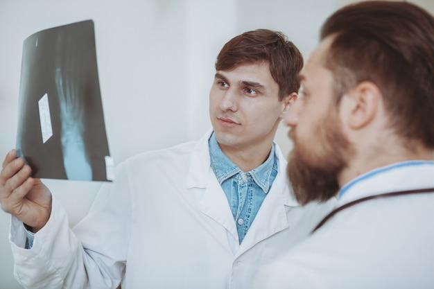 Close-up de um dois médicos do sexo masculino se concentrando, examinando a radiografia de um paciente