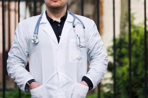 Close-up, de, um, doutor masculino, com, estetoscópio, ao redor, seu, pescoço, ao ar livre
