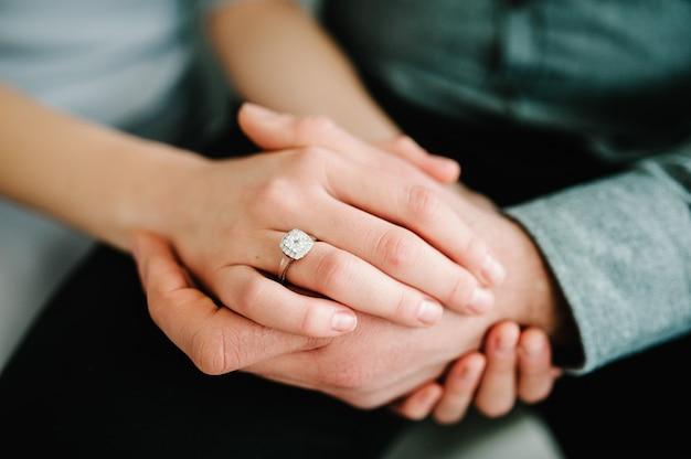 Close up de um elegante anel de diamante de noivado no amor de dedo de mulher e conceito de casamento