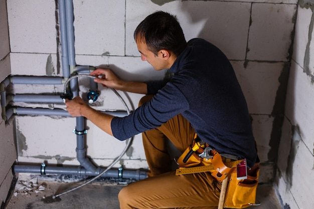 Close-up de um encanador masculino conserta canos no banheiro