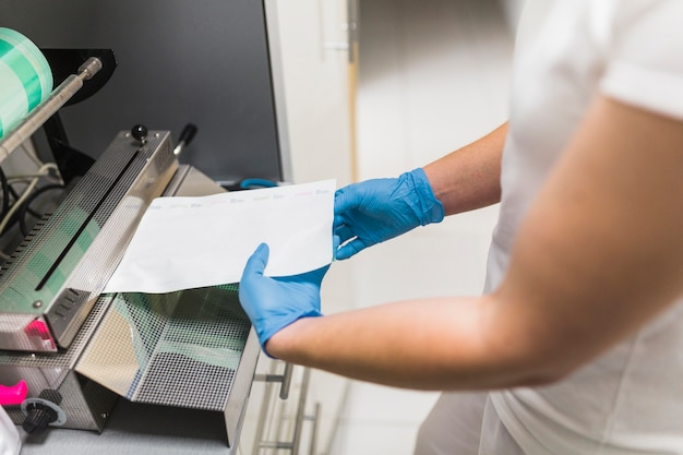 Close-up, de, um, enfermeira, mão, trabalhar, ligado, pouch, sealer, embalagem, maquinaria