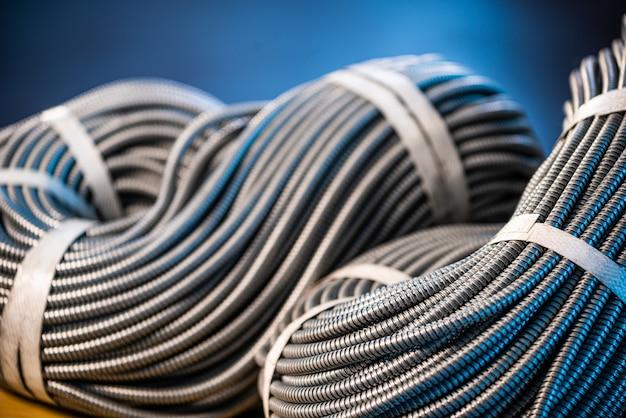 Close-up de um enorme feixe de tubos flexíveis de metal interconectados na produção. o conceito de dispositivos eletrônicos modernos de alta tensão e produção especializada