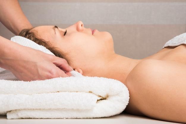 Close-up, de, um, esteticista, mão, embrulhando toalha, ligado, mulher, cabeça