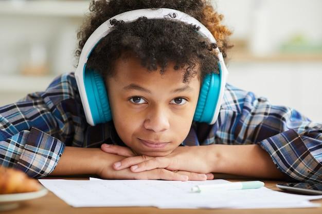 Close-up de um estudante africano com cabelo encaracolado em fones de ouvido, olhando enquanto está sentado à mesa e estudando