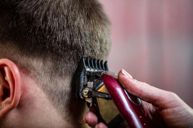Close-up de um estudante do sexo masculino a cortar o cabelo com máquina de cortar cabelo