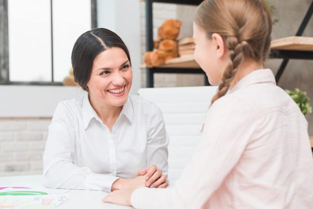 Close-up, de, um, feliz, jovem, femininas, psicólogo, e, menina, falando, um ao outro, durante, terapia, sessão