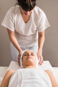 Close-up, de, um, femininas, terapeuta, embrulhando toalha, ligado, mulher, cabeça