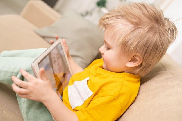 Close-up de um filho fofo com cabelo loiro sentado no sofá e usando um tablet enquanto conversa com a mãe online