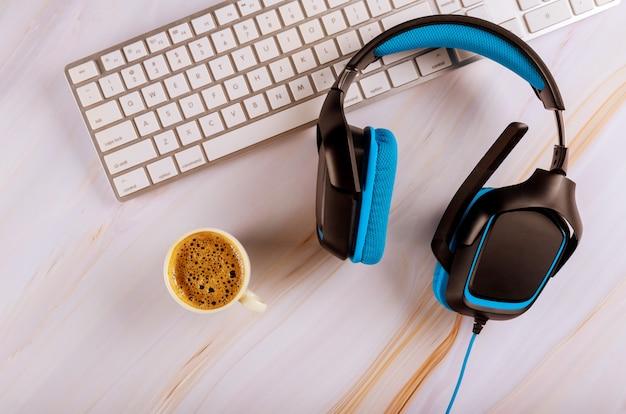 Close-up de um fone de ouvido estéreo no teclado de um computador na mesa de escritório com uma xícara de café