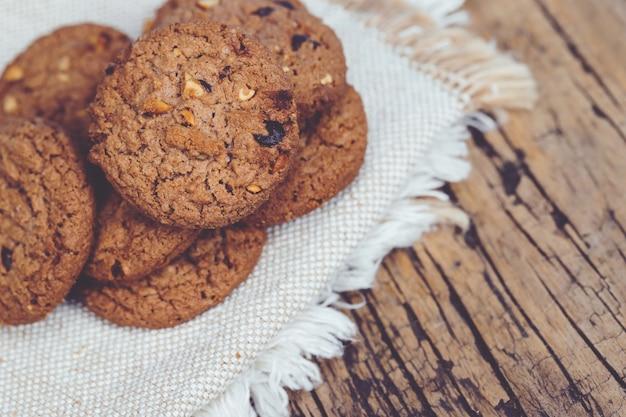 Close up de um grupo biscoitos de chocolate muitos empilhados no avental pano de saco escuro velho rústico mesa de prancha de madeira