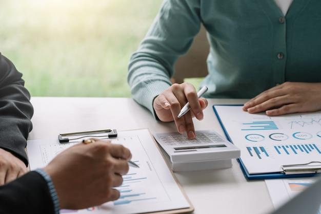 Close-up de um grupo de empresário e empresária mãos brainstorming juntos usando gráfico calculadora tablet trabalhar no escritório.