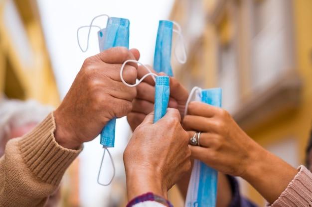 Close up de um grupo de quatro mãos juntas segurando uma máscara médica e cirúrgica após winnig covid-19 e ser livre e não pode usar máscara na rua