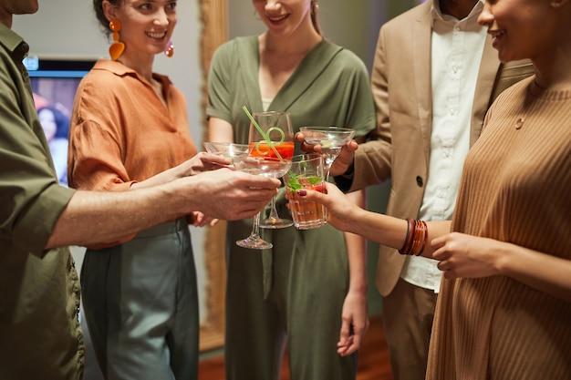 Close-up de um grupo diversificado de amigos batendo copos enquanto brinda em uma festa interna, copie o espaço