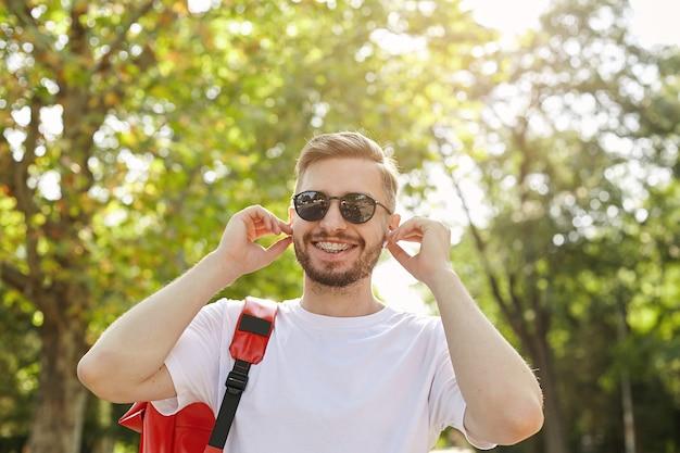 Close-up de um hipster feliz caminhando pelo parque em um dia de sol, usando óculos escuros e camiseta branca, colocando fones de ouvido nas orelhas, estando de bom humor