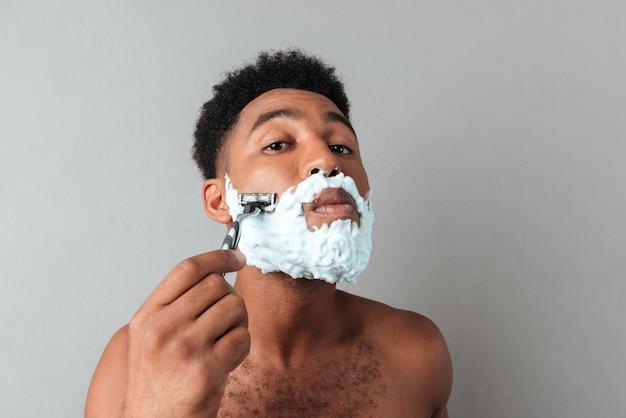 Close-up de um homem africano nu concentrado de barbear