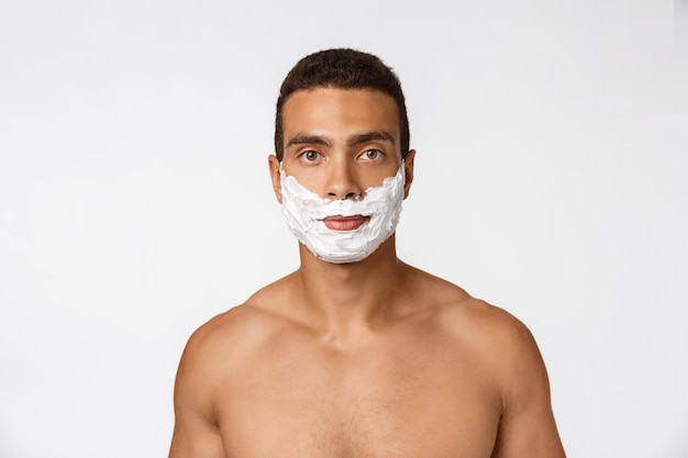 Close-up de um homem africano nu feliz com o rosto na espuma de barbear isolado