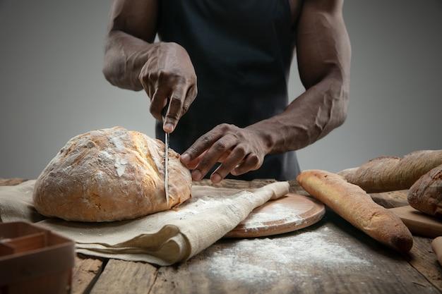 Close-up de um homem afro-americano cortando pão fresco com uma faca de cozinha