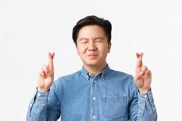 Close-up de um homem asiático preocupado e esperançoso fecha os olhos e cruza os dedos para dar boa sorte, fazendo um desejo, rezando enquanto espera pelos resultados, antecipando notícias, parede branca em pé