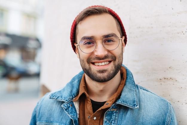 Close-up de um homem barbudo elegante jovem feliz e bonito caminhando ao ar livre na rua