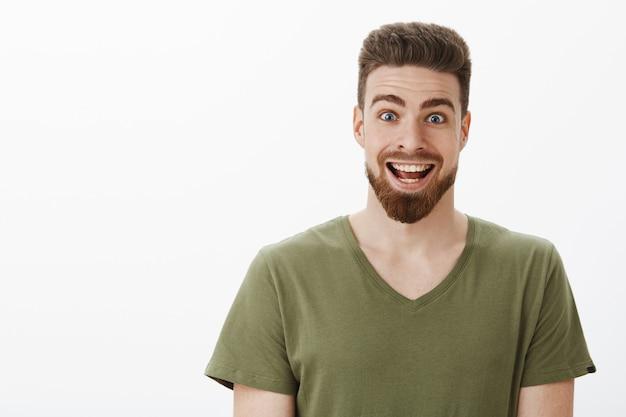 Close-up de um homem barbudo feliz, surpreso e animado, erguendo as sobrancelhas e arregalando os olhos, sorrindo amplamente ao receber uma oferta incrível e inesperada de toda a vida sobre uma parede branca