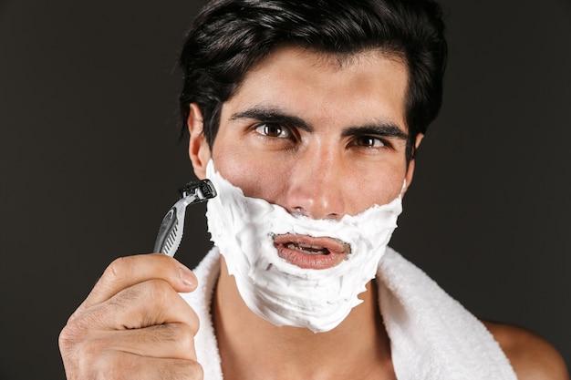 Close-up de um homem bonito sem camisa, isolado, enrolado em uma toalha, segurando uma navalha, fazendo a barba