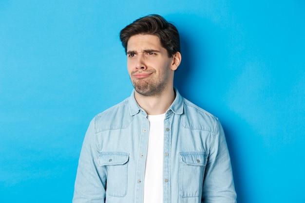 Close-up de um homem chateado e desapontado fazendo careta, olhando para a esquerda insatisfeito, encolhendo-se do banner promocional ruim, em pé sobre um fundo azul.